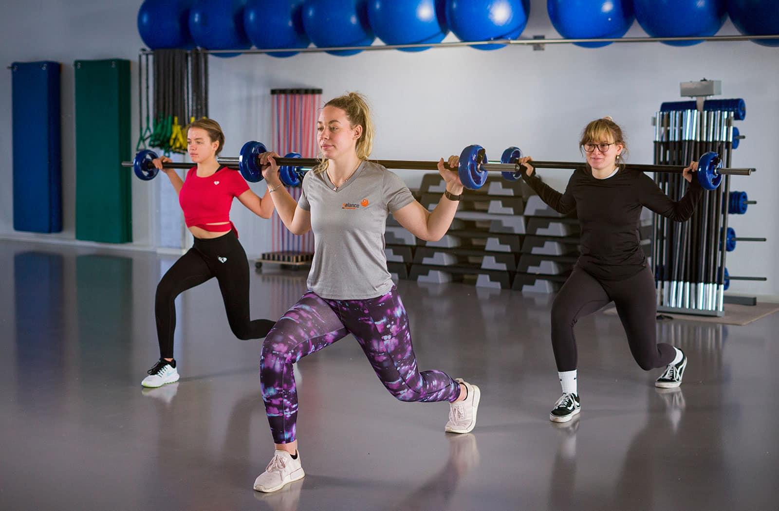 Motivierendes Fitness-Training in Gruppe. Kraftvolle Übungen mit der Langhantel.