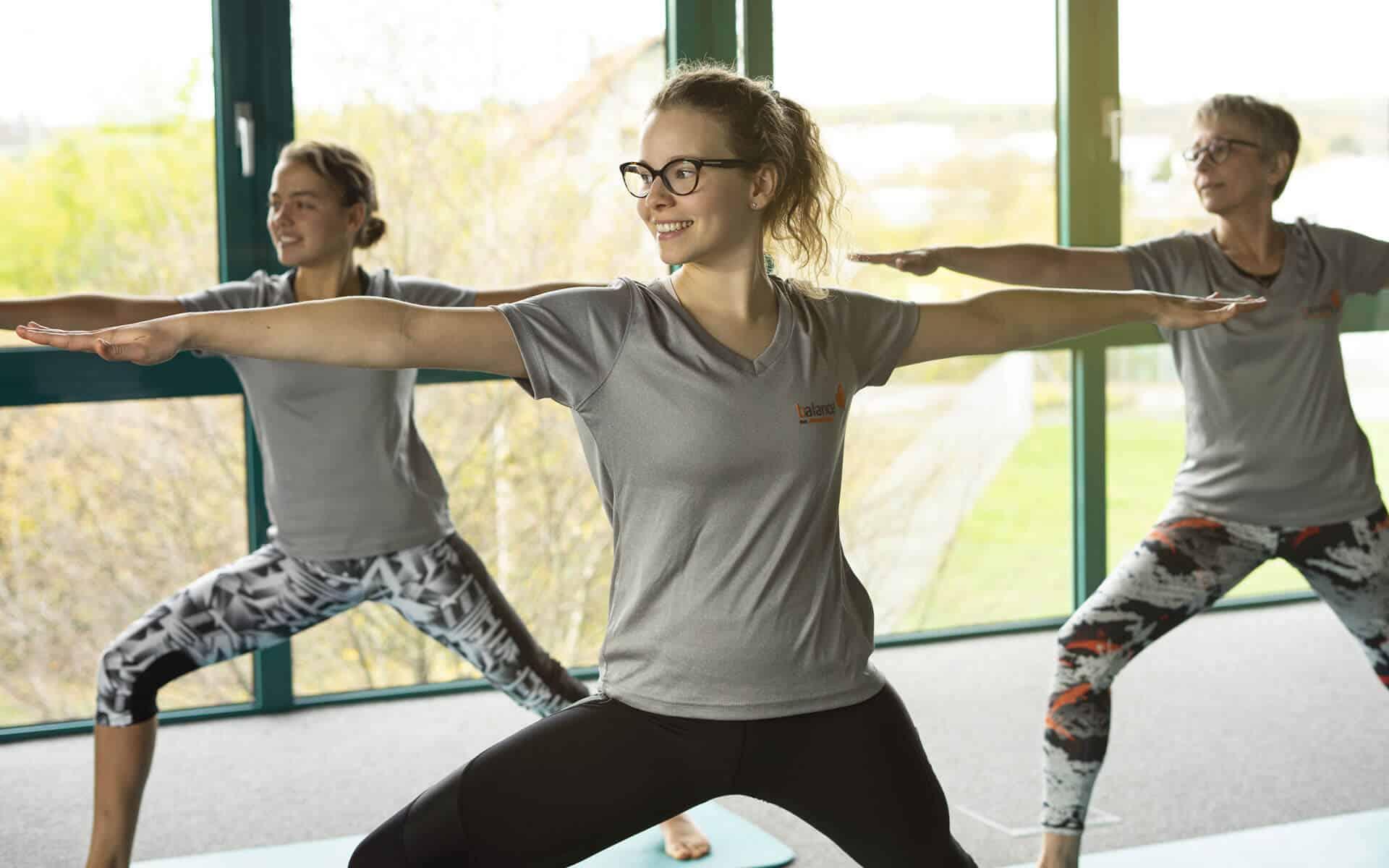 Die Yoga Trainerinnen Hannah Markgraf und Brigitte Lemsch demonstrieren gemeinsam mit Daniela Firsching eine Pose aus dem Yoga. Unterschiedliche Yogakurse werden mehrmals die Woche im Kursraum 2 im balance Fitnessstudio in Kitzingen angeboten.