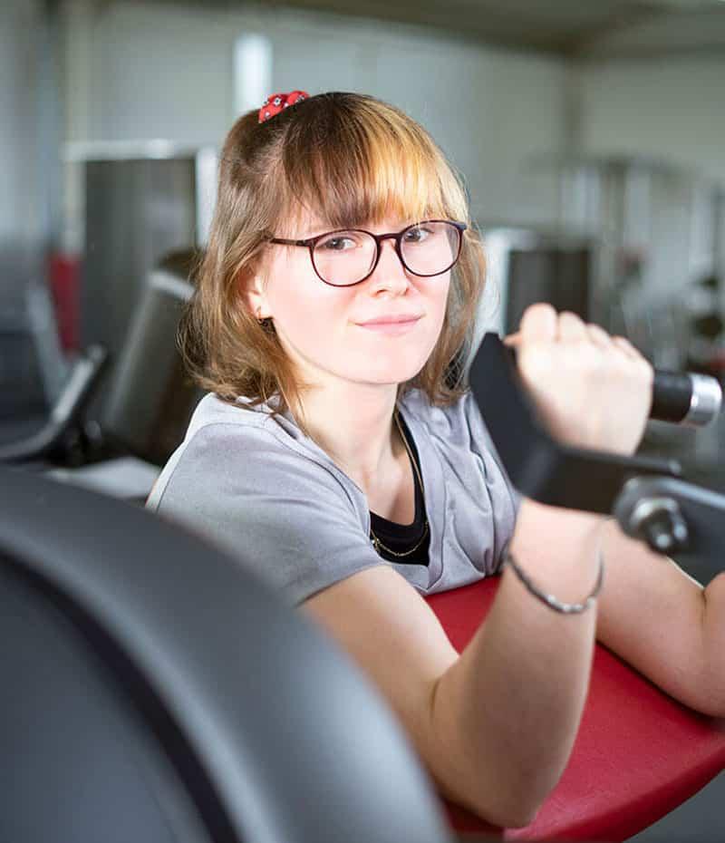 Sophie Kolb demonstriert den Ablauf der Übung an der Bizepsmaschine. Das Training an dem Gerät kräftigt die Armmuskulatur und ist ein Teil des Ganzkörpertrainings der 4E-Zirkeleinheit im Fitnesscenter.
