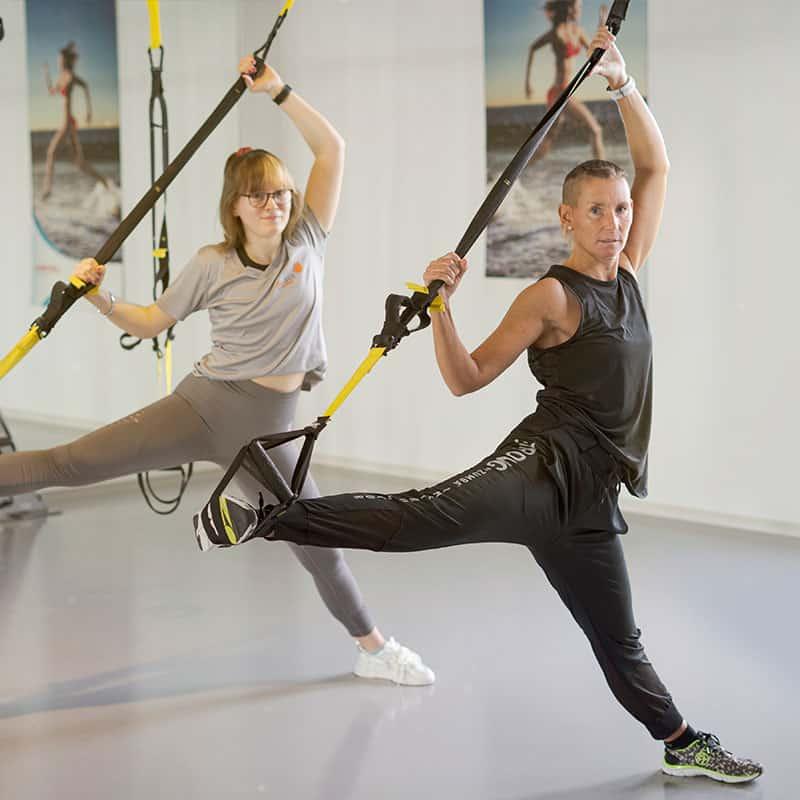 Kerstin Hirschleb und Sophie Kolb demonstrieren eine Übung beim TRX Yoga im Kursraum 1 der balance Fitnesslounge.